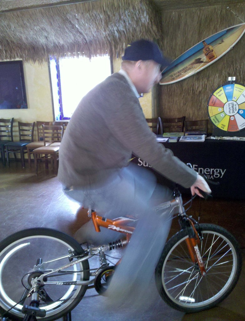 T.J. Zane, President & CEO of the Lincoln Club of San Diego County, takes a ride on the California Center for Sustainable Energy's electricity generation bike at the April Albondigas Club meeting.